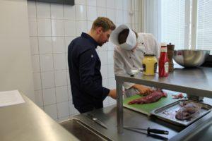 Benedikt Holzhinrich (links) schaute den Teilnehmern des Seminars beim Zubereiten des Rindfleischs genau auf die Finger. Foto: Köcheclub Münsterland e.V.