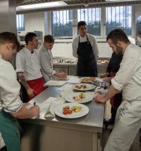 Die Koch-Azubis versammeln sich um ihre Teller und besprechen die Ergebnisse. Foto: VKD
